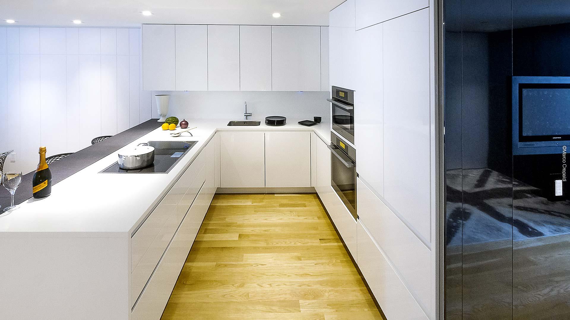 Cucina in Corian e legno pregiato con disposizione angolare
